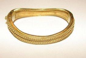 12: 18K yellow gold hinged bangle bracelet.
