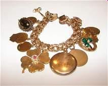 23: 12 K gold filled charm bracelet. Total 12 charms.