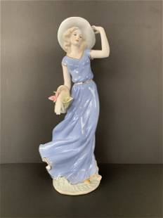 Beautiful porcelain lady statue with flowers.