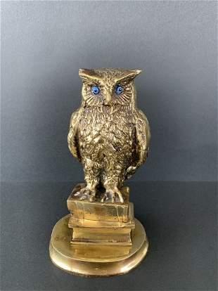 Bronze sculpture of owl standing on books