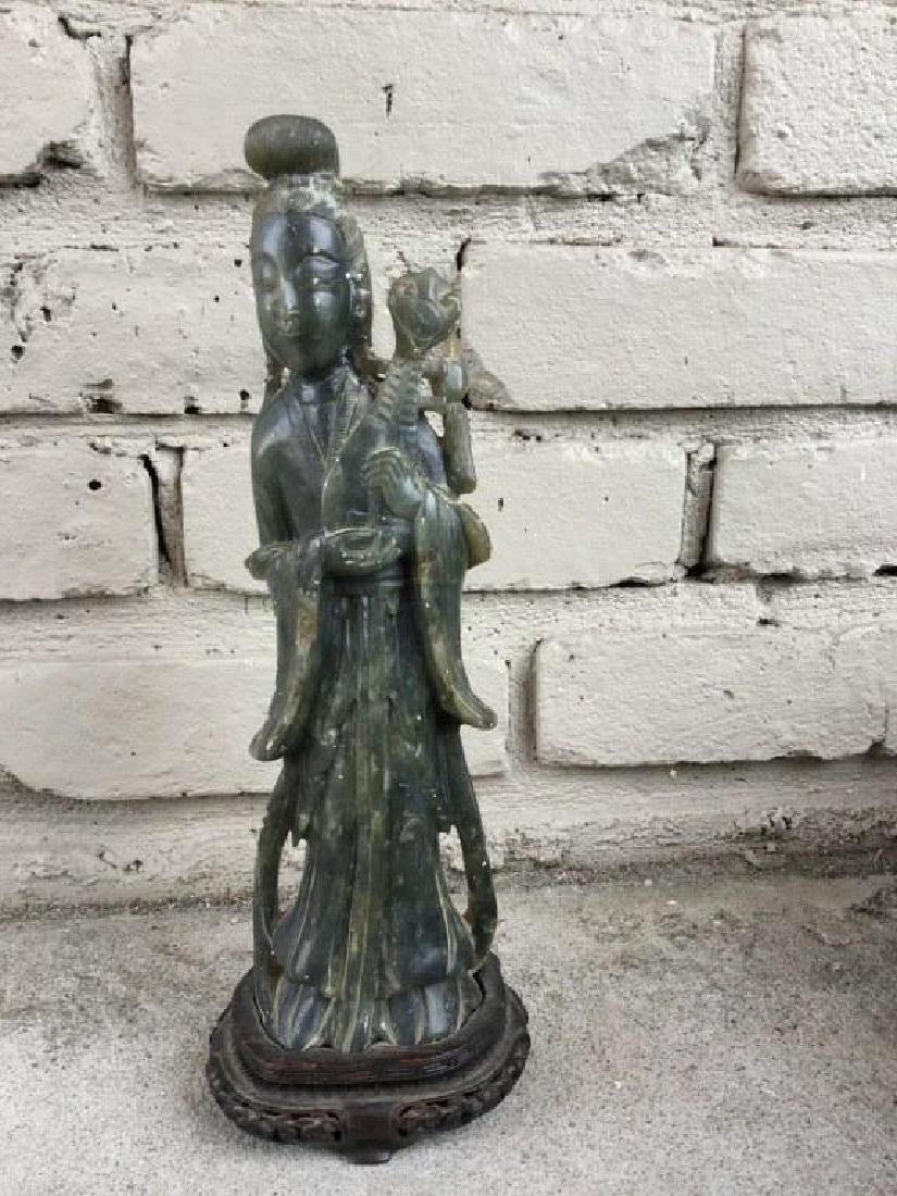 JADE FIGURE HOLDING AN INSTRUMENT, SMALL HOLE DRILLED