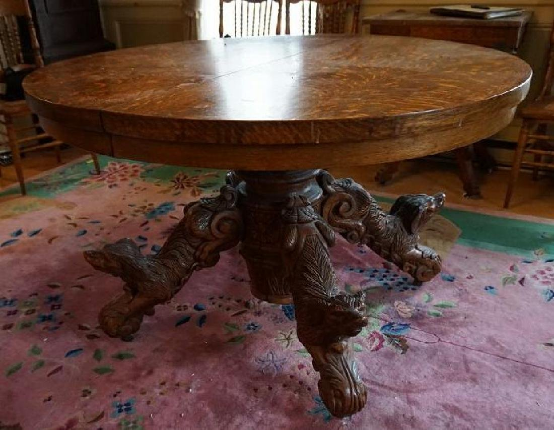QUALITY ROUND OAK DINING TABLE W/CARVED DOGS ON BASE,