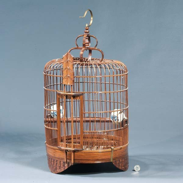 16: Wicker birdcage with blue and white ceramic pots.