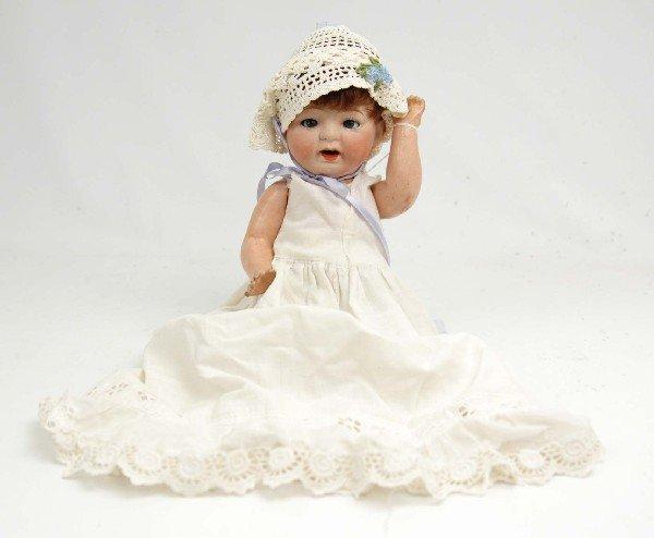 619: Bisque head doll, brunette hair, blue sleep eyes,