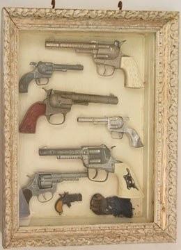 244: Shadow box display case with seven toy guns