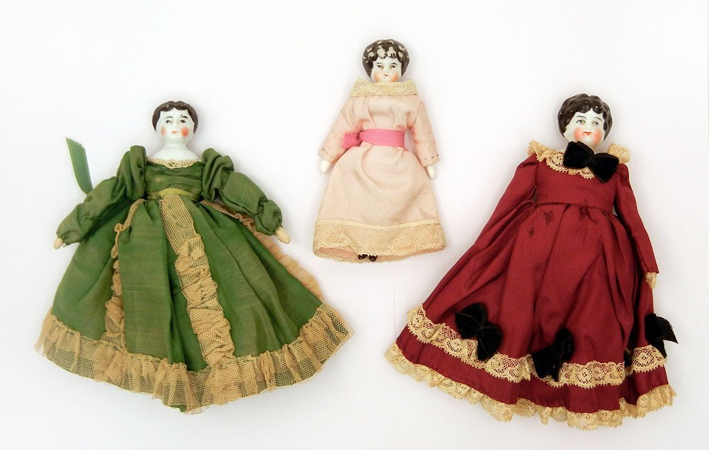 46: Three china head dolls, two with original clothes,