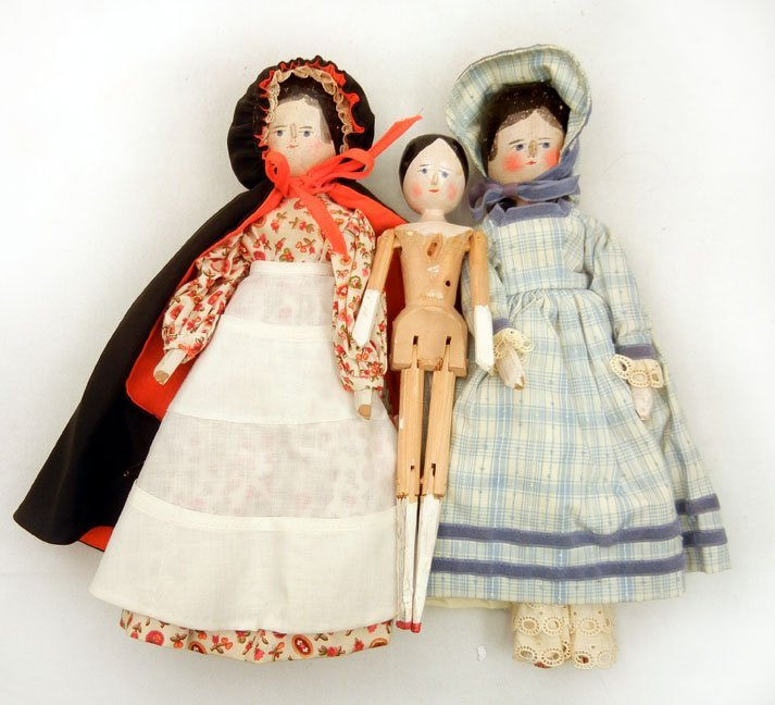 56: Three old peg wooden dolls, wearing newer outfits,