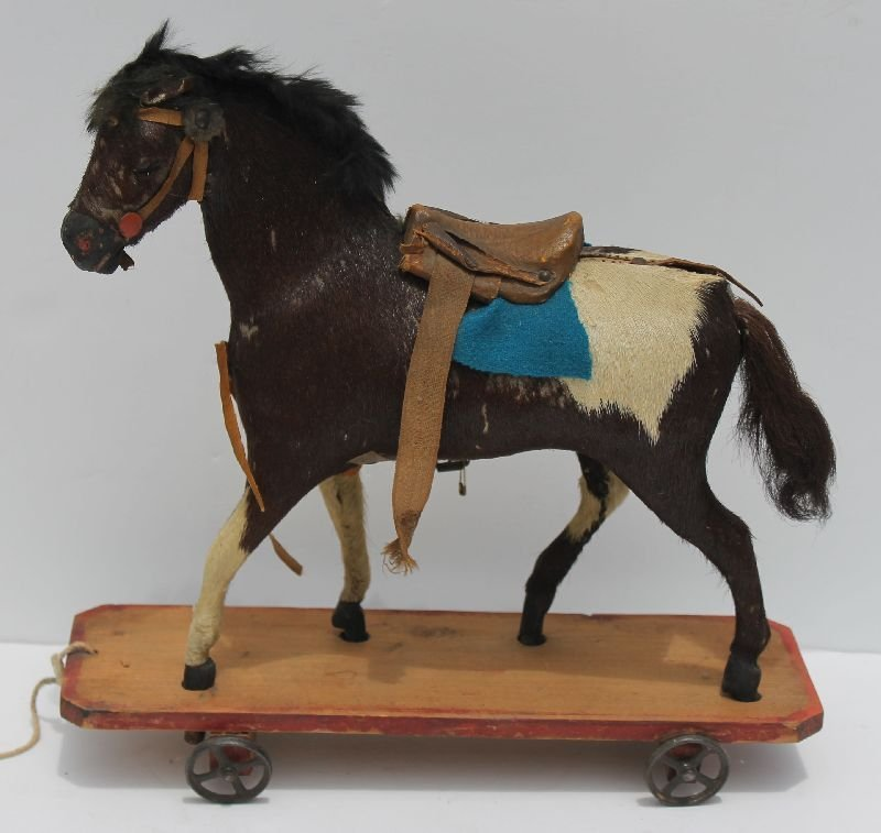 Rare 19thC hide covered horse pull toy on orig painted
