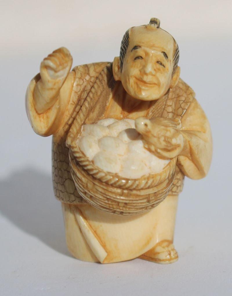 Japanese 2 color sgnd carved Netsuke of an egg seller -