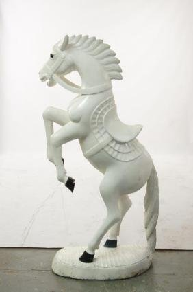 A wood carved white rearing horse statue
