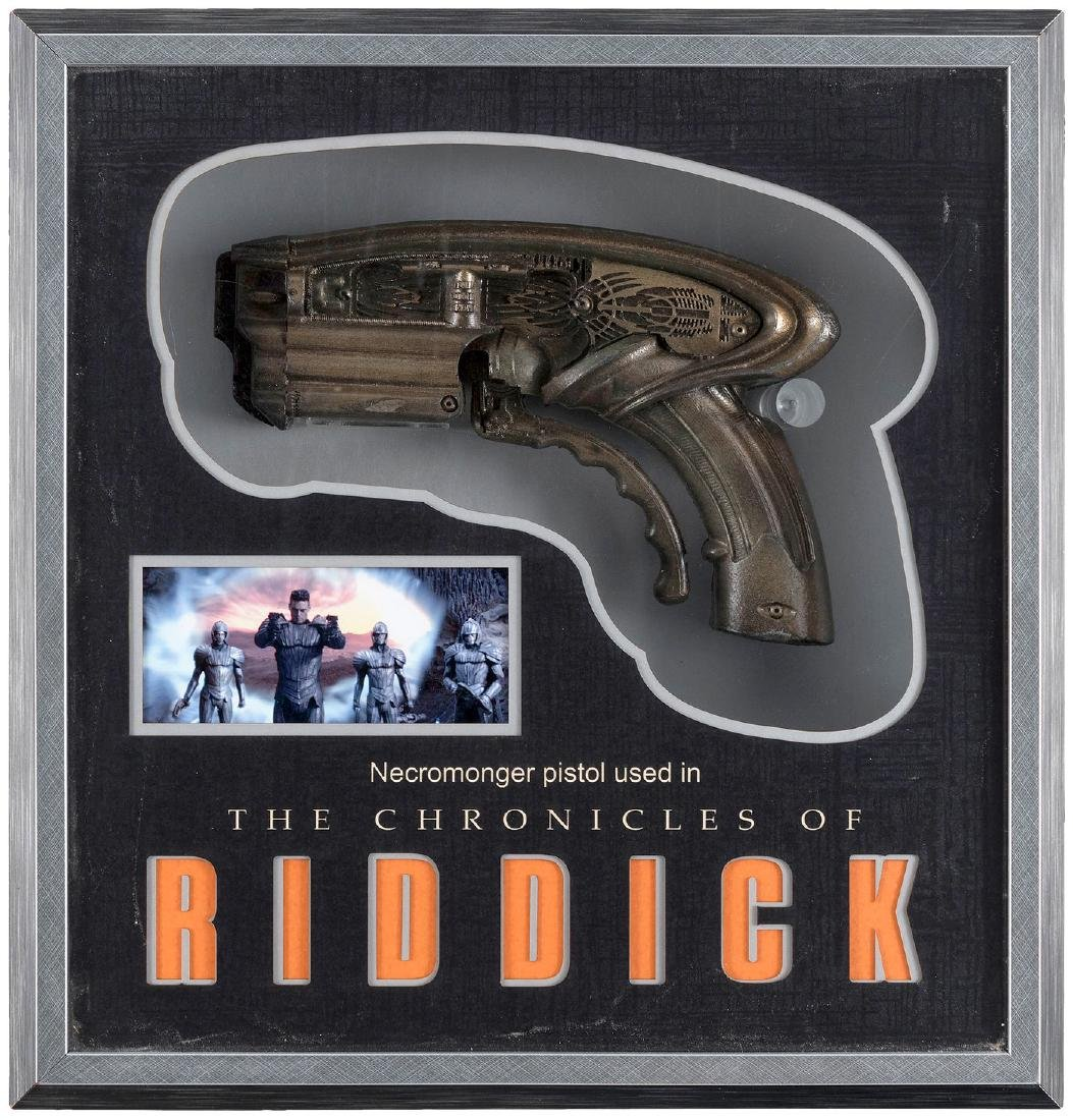 CHRONICLES OF RIDDICK PROP PISTOL WEAPON IN DISPLAY CASE.