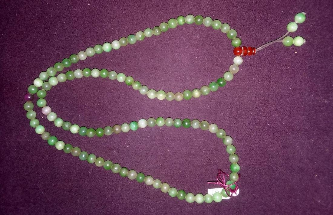 A FAR EASTERN CARVED JADE AND MULTI STONE NECKLACE,