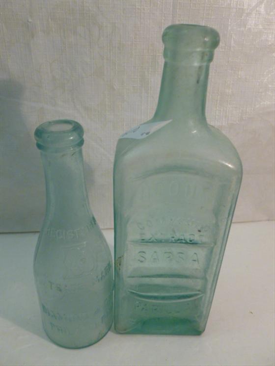 2 antique glass bottles pale blue in color