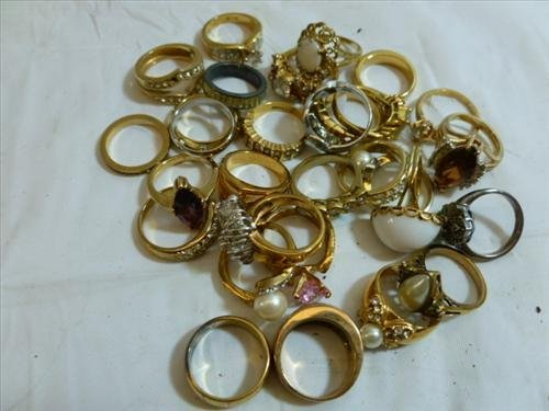 Container full of assorted rings gold and silver tone