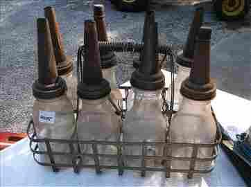 8 VINTAGE GLASS OIL BOTTLES W/METAL SPOUTS IN BASKET