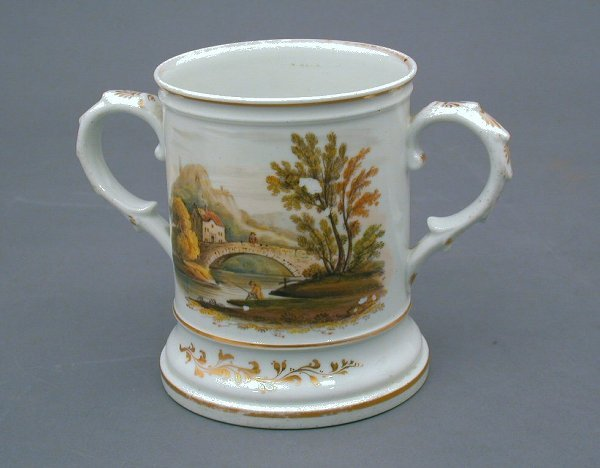 26: An English porcelain twin handled cup, wi
