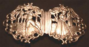 A silver golfing belt buckle, in two sections, each
