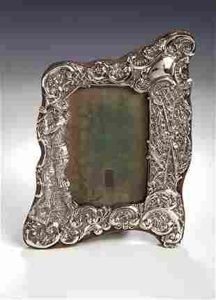 A late Victorian silver photograph frame, repousse
