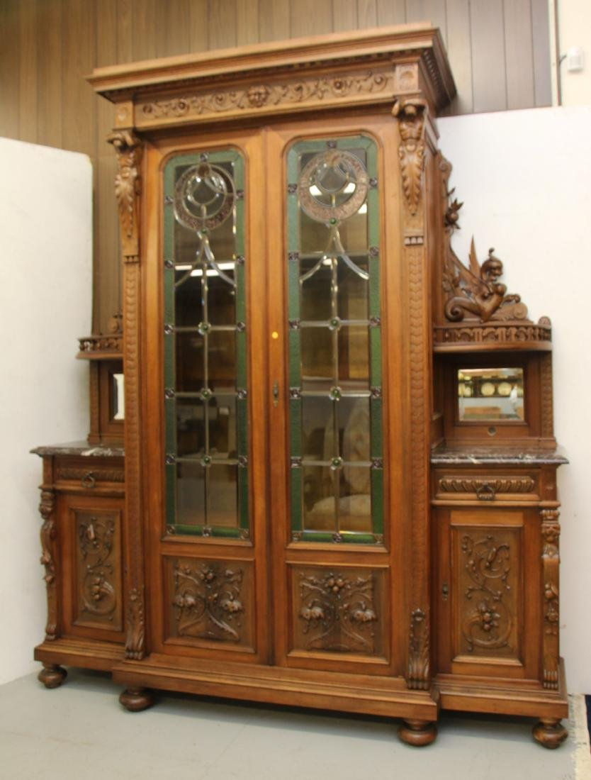CARVED WALNUT CABINET WITH LEADED GLASS DOORS