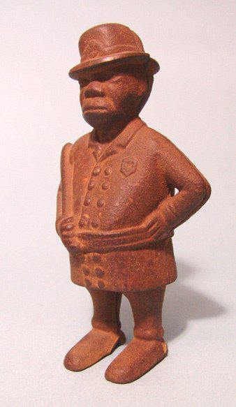 2006: Antique iron policeman bank. Officer stands holdi