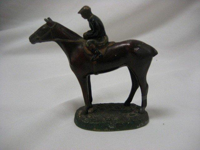 7: Painted statue of a jockey on a horse.  Some paint l