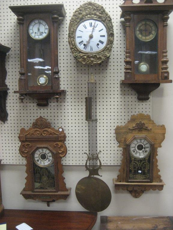 Wag-on-wall clock with ornate brass floral frame and