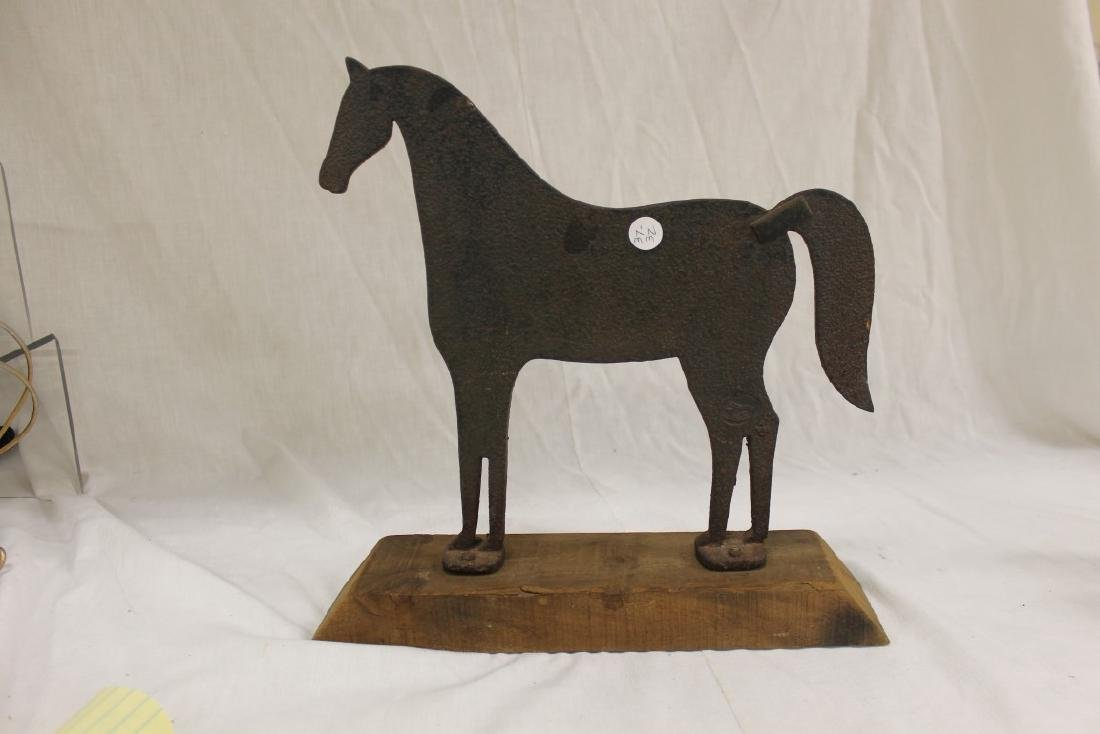 Mounted sheet iron horse on wooden base, with strap at