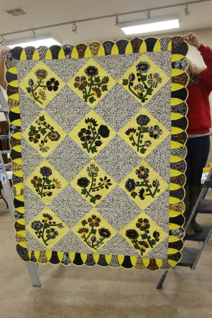 Quilt with black and yellow Morning Glory type flowers,