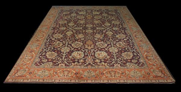 20C: HAND KNOTTED WOOL RUG IN RUST, WHEAT AND PLUM