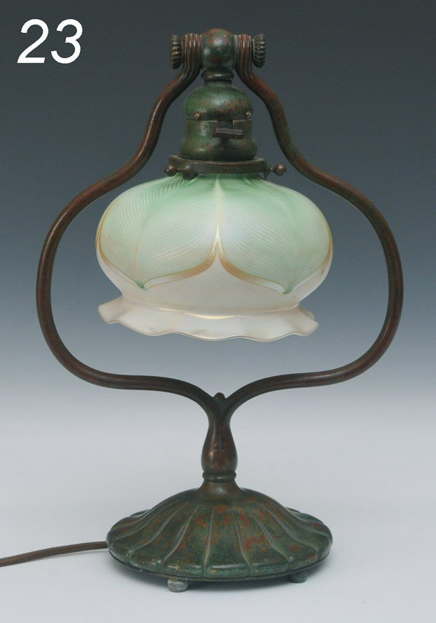 23: TIFFANY STUDIOS BRONZE DESK LAMP with feathered Que