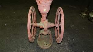 Primitive table top coffee grinder as seen yard art