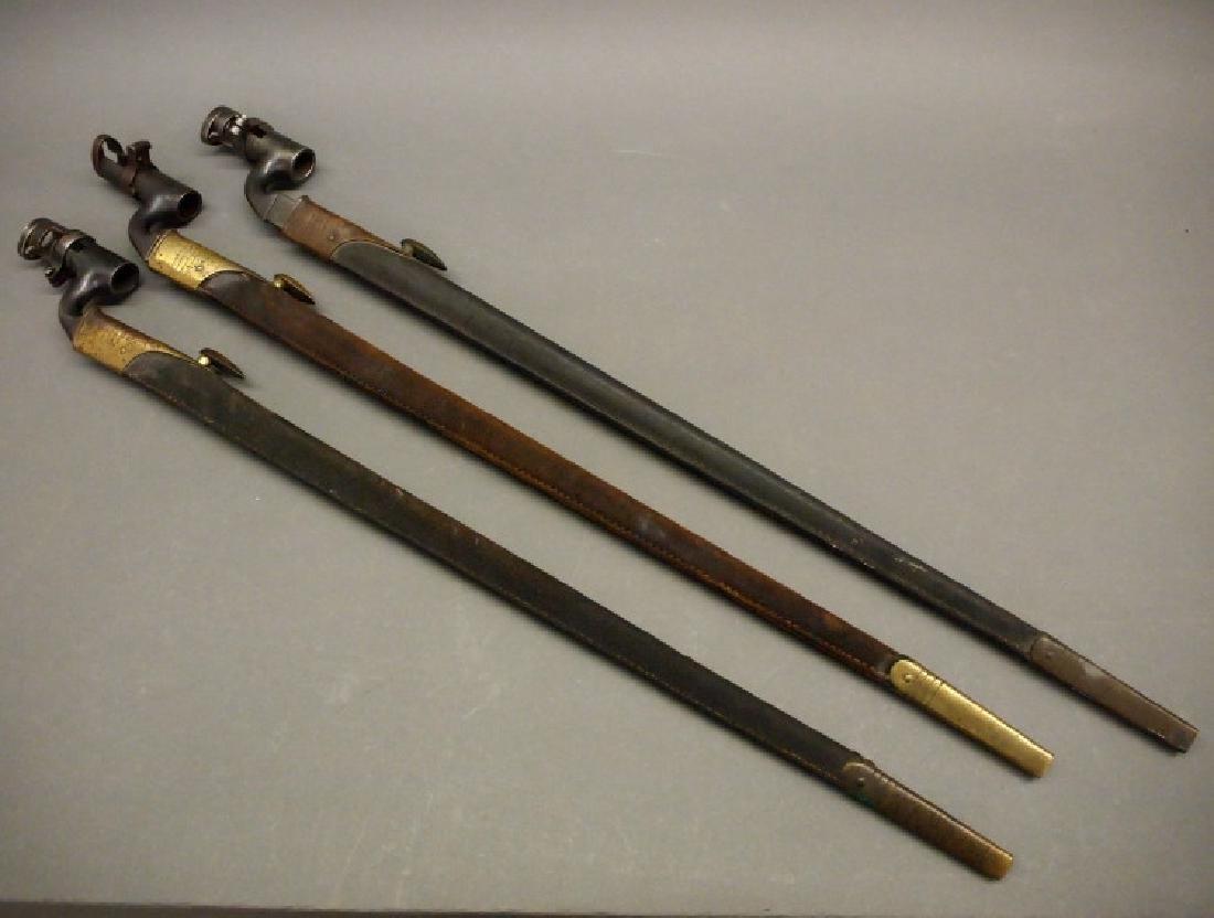 Three socket bayonets with scabbards