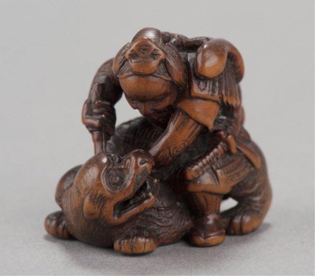 A carved boxwood netsuke of ii no hayata slaying t