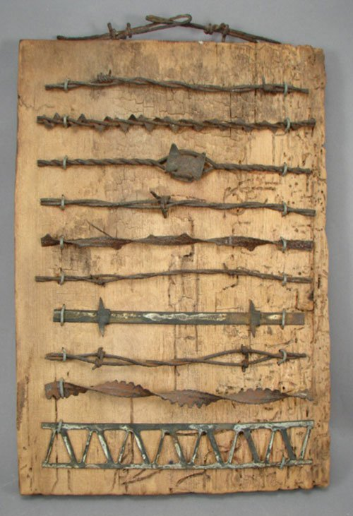 Antique barbed wire examples mounted on pine boar