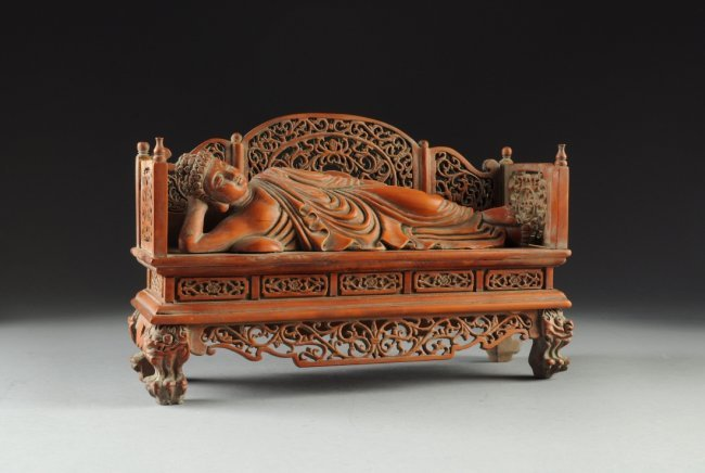 A chinese boxwood carved buddha reclining on bed t