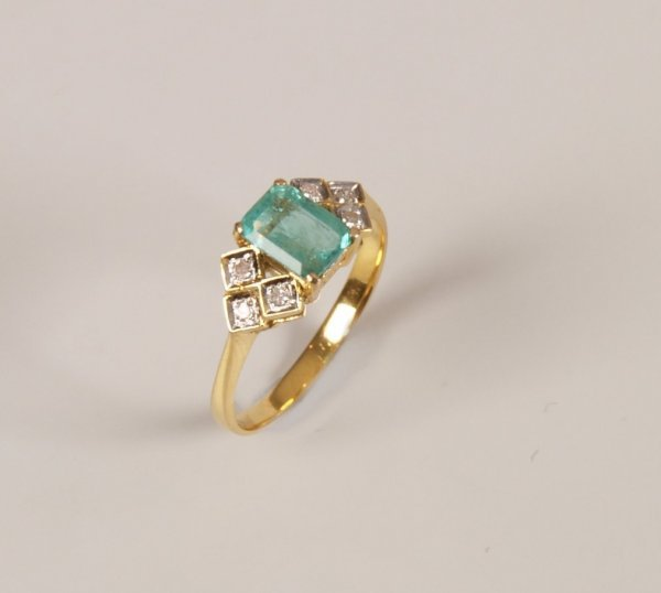 466 a rectangular emerald ring with three diamonds to